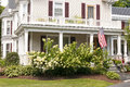 New england house porch an old with a large white bay windows and flowers for landscaping Stock Photos