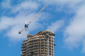 New high rise building under construction with a crane sky and clouds on the background Stock Images
