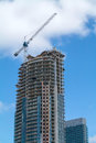New high rise building under construction with a crane sky and clouds on the background Stock Photos