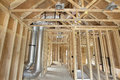 New home construction framed with wood studs framing heating cooling system air duct works plumbing and electrical ceiling light Stock Photos
