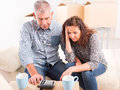 New home mature couple at sitting and using calculator to sum their expenses and loans Stock Image