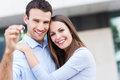 New home owners with key couple hugging keys to house Royalty Free Stock Image