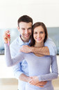 New home owners with key young couple hugging at Royalty Free Stock Photography