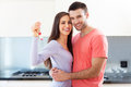 New home owners with key young couple hugging at Stock Photos