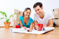 New home plans couple lying on floor looking at of house together while drinking coffee and laughing Royalty Free Stock Photography