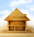 New home a wooden cut out of a house on a wooden floor with a blue cloudy backdrop concept for building a wooden or cabin Stock Images
