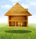 New home a wooden cut out of a house on a wooden floor with a blue cloudy backdrop a man and a woman are inside the concept for Royalty Free Stock Images