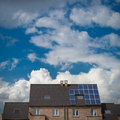 New houses with solar panels on roof under blue sky and clouds Stock Photos