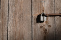 The new iron lock on an old metal fixing hangs on a high wooden gate Royalty Free Stock Photo