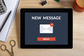 New message concept on tablet screen with office objects Royalty Free Stock Photo