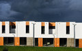 New modern family houses in a row just built illuminated under dramatic stormy dark blue sky Stock Photography