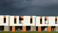 New modern family houses in a row just built illuminated under dramatic stormy dark blue sky Royalty Free Stock Photos