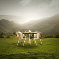 New philosophy a modern table and four chairs outdoor on the grass with a wonderful mountains panoramic view at sunset Royalty Free Stock Images