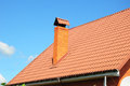 New red metal roof tile and smokestack against blue sky Royalty Free Stock Photography