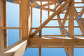 New residential wooden construction home framing against a blue sky. Royalty Free Stock Photo