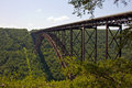 New river gorge bridge and trees spanning the green forest covered blue sky white clouds Royalty Free Stock Image