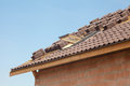 New roof with open skylight, natural red tile against blue sky. Royalty Free Stock Photo