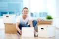 New settler a young guy with blank paper sitting on the floor of house surrounded with boxes Stock Photography