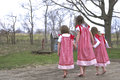 New spring dresses three sisters walking hand in hand barefoot in handmade red and white Royalty Free Stock Image