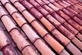 New terracotta tiles laid on a roof, partially painted red. Royalty Free Stock Photo