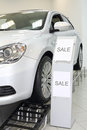 New white shining beautiful car stands on special stand in shop Royalty Free Stock Photos