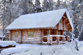 New wooden Russian sauna in a snowy winter forest, sunny day. Royalty Free Stock Photo