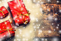 New Year background gift red box with presents on wooden board with snow Royalty Free Stock Photo
