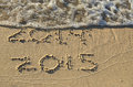 New year on beach fro written in sand with foamy surf Royalty Free Stock Photos