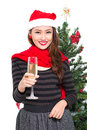 New year celebrating vertical portrait of a young woman in a santa hat with a glass of champagne Stock Image