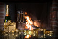 New year celebration two champagne glasses and gift boxes in front of fireplace Stock Photography