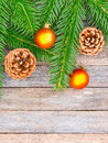 New Year or Christmas background: fir branches, goldish glass balls cones over old wooden backdrop Royalty Free Stock Photo