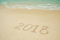 New Year 2018 is coming 2018 on a beach sand, the wave