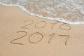 New Year 2017 is coming concept - inscription 2016 and 2017 on a beach sand, the wave is almost covering the digits 2016
