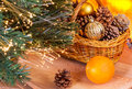 New year composition near the fireplace basket with pine cones and christmas balls under tree a Royalty Free Stock Photo