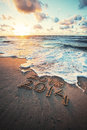 New year concept inscription and on a beach sand the wave is covering numbers Royalty Free Stock Photo