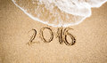 New year digits written on seashore and being washed off by wave Royalty Free Stock Photography