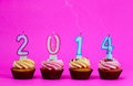 New year is end cupcakes with candles on the colored background Royalty Free Stock Photo