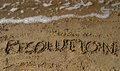 New year s resolution written in sand the word on the beach with ocean waves background Stock Images