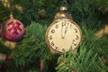 New year time vintage alarm clock toy on the christmas tree with arrows at twelwe Royalty Free Stock Images