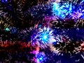 New Year tinsel with neon lights on a Christmas tree closeup Royalty Free Stock Photo