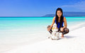 New year in the tropics young girl sitting on a beautiful tropical beach next to a snowman made ​​of sand Royalty Free Stock Photography