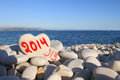 New year written on heart shaped stone on the beach with spray brush Royalty Free Stock Image