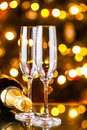 New years preparations champagne glasses and the bottle with holiday lights in the background Stock Image