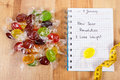 New years resolutions written in notebook, candies and tape measure Royalty Free Stock Photo
