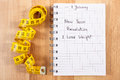 New years resolutions written in notebook and tape measure Royalty Free Stock Photo