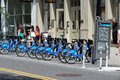 New york bicycle sharing july people walk past citibike station on july in with stations and bicycles it is one of top Royalty Free Stock Images