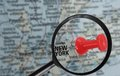 New york map closeup of a red push pin in a of city under a magnifying glass Stock Photo