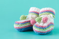 Newborn announcement. knitted baby booties on plain blue backgro