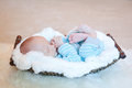 Newborn asleep in basket cute little baby laying lined with soft white fuzzy blanket Stock Photos
