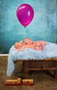 Newborn babies with balloon adorable twin asleep and holding a pink Royalty Free Stock Photo